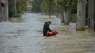Un pompier aide un passant dans une rue inondée, le 15 octobre 2018, à Trèbes (Aude). (PASCAL PAVANI / AFP)