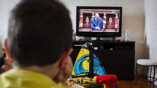 Un enfant regarde le discours d'Edouard Philippe à l'Assemblée nationale, le 28 avril 2020. (MAXIME FRAISSE / HANS LUCAS / AFP)