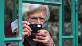 """Le photoreporter Marc Riboud prend la pose, au Musée de la vie romantique, à Paris, le 10 mars 2009, pour l'ouverture de son exposition """"L'instinct de l'instant"""". (JOEL SAGET / AFP)"""
