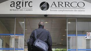 Un homme entre au siège des organismes de retraites complémentaires, Agirc et Arrco, le 16 octobre 2012 à Paris. (KENZO TRIBOUILLARD / AFP)