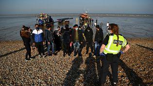 Des migrants escortés par les autorités britanniques à leur arrivée sur le sol de Dungeness, en Angleterre, le 7 septembre 2021. (BEN STANSALL / AFP)