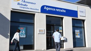 """Deux personnes passent devant l'agence """"Assurance-retraite"""" du Languedoc-Roussillon dans la ville de Le Cres, le 22 mars 2019 (PASCAL GUYOT / AFP)"""
