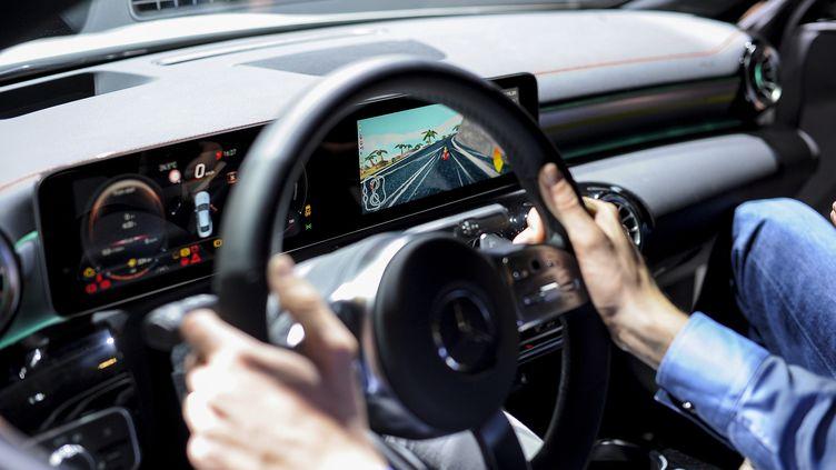 Un parlementaire américain teste une voiture de course Mercedes Benz, durant le Mondial de l'automobile à Barcelone (Espagne), le 25 février 2019. (JOAN CROS / NURPHOTO / AFP)