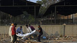 Des bénévoles préparent le corps d'un homme mort du Covid-19 avant le rituel de la crémation, le 12 mai 2021 à New Delhi. (ARUN SANKAR / AFP)