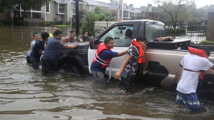 Des habitants de Houston poussent un pick-up dans une rue inondée, le 27 août 2017, après le passage de la tempête Harvey sur le Texas (Etats-Unis). (JOE RAEDLE / GETTY IMAGES NORTH AMERICA / AFP)