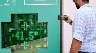 Un passant prend en photo le thermomètre électronique installé à l'extérieur d'une pharmacie à Paris le 25 juillet 2019. (BERTRAND GUAY / AFP)