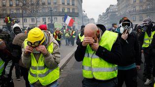 """Des manifestants recoivent des tirs de gaz lacrymogènes, lors de la 8e journée de mobilisation des """"gilets jaunes"""" à Paris, le 5 janvier 2019. (MARIE MAGNIN / HANS LUCAS / AFP)"""