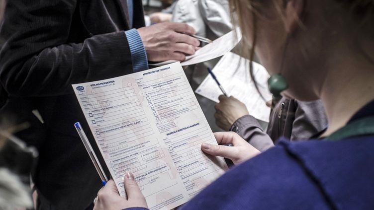 Une électrice s'apprête à remplir une demande de procuration, le 11 avril 2012, dans un commissariat de police de Lyon (Rhône). (JEAN-PHILIPPE KSIAZEK / AFP)