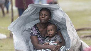 Une femme et un enfant se protègentcontre les intempéries, le 17 août 2021 près des Cayes, quelques jours après le séisme qui a frappé Haïti. (REGINALD LOUISSAINT JR / AFP)