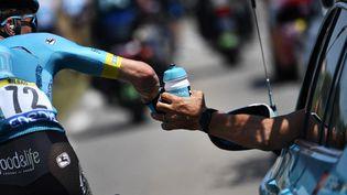Peio Bilbao attrape un bidon lors du Tour de France 2019, le 24 juillet 2019. (JEFF PACHOUD / AFP)
