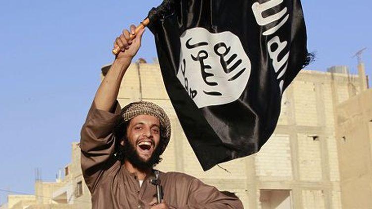 En Syrie, un combattant de l'Etat islamique défile le drapeau à la main. (REUTERS PHOTO / STRINGER)