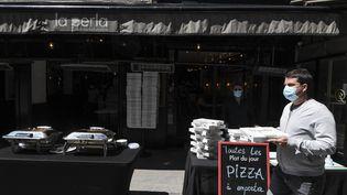 Un homme achète une pizza à emporter, à Paris, le 18 mai 2020. (ALAIN JOCARD / AFP)
