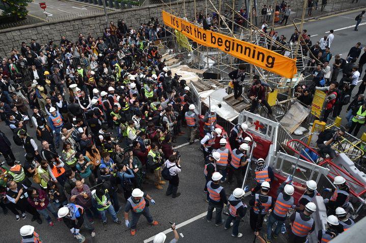 Les médias observent les autorités en train de démonter le camp d'occupation des manifestants, le 11 décembre 2014, à Hong Kong. (PEDRO UGARTE / AFP)