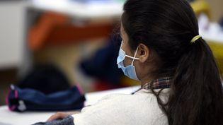 Uneélève de collège porte un masque chirurgical de protection dans sa salle de classe. Depuis le 2 novembre, le masque est également obligatoire pour les élèves de primaire. (ALEXANDRE MARCHI / MAXPPP)
