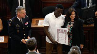 Mamoudou Gassama reçoit la médaille Grand Vermeil des mains de la maire de Paris, Anne Hidalgo, le 4 juin 2018. (FRANCOIS GUILLOT / AFP)