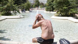 Un homme se rafraîchit, le 1er juillet 2015 à Lyon, lors d'un épisode de canicule. (ROMAIN LAFABREGUE / AFP)