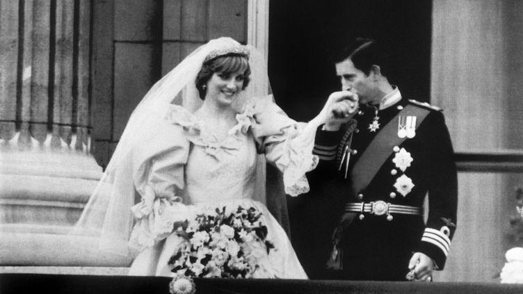 Le prince Charles baise la main de son épouse Diana sur le balcon de Buckingham Palace à Londres (Royaume-Uni) après leur mariage, le 29 juillet 1981. (ARCHIVE / UPI / AFP)