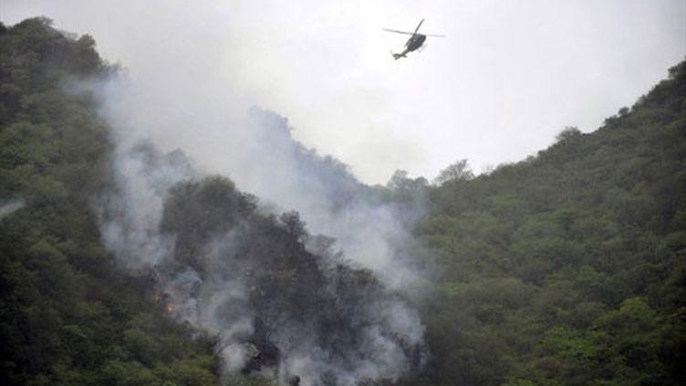 Un hélicoptère survole la zone où un avion de ligne s'est écrasé, près d'Islamabad (28 juillet 2010) (AFP / Aamir Qureshi)