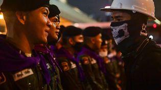 Un manifestant prodémocratie devant des policiers lors d'un rassemblement contre le gouvernement, le 21 octobre 2020, à Bangkok (Thaïlande). (LILLIAN SUWANRUMPHA / AFP)