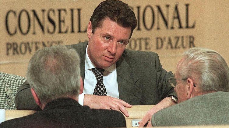 Christian Estrosi, président du groupe RPR àla région Provence-Alpes-Côte d'Azur, s'entretient avec des conseillers régionaux de sa formation, le 20 mars 1998 dans l'hémicycle du conseil régional, à Marseille. (GEORGES GOBET / AFP)