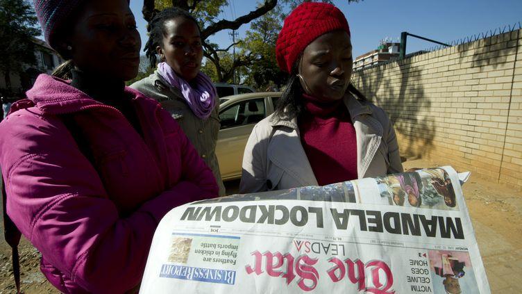 Des Sud-Africaines devant l'hôpital où serait hospitalisé Nelson Mandela, à Pretoria, le10 juin 2013. (ALEXANDER JOE / AFP)