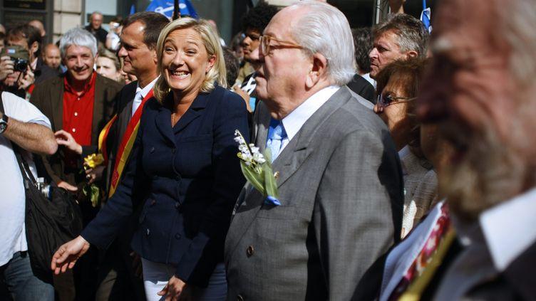 Philippe Péninque, en chemise rouge au deuxième plan, photographié ici lors du défilé du FN le 1er mai 2011 à Paris, est un proche de Marine Le Pen, présidente du Front national. ( MAXPPP)