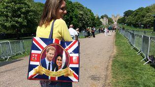 Une habitante de Windsor portant un sac imprimé avec la photo du futur couple princier Harry et Meghan Markle, sur le chemin du Long Walk au château de Windsor, le 17 mai 2018. (TERESA DAPP / DPA)