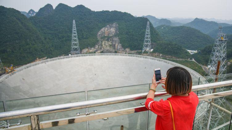 Une femme prend en photo le radiotéléscope FAST, dans la province de Guizhou (sud-ouest de la Chine), le 7 septembre 2016. (LI XU / XINHUA / AFP)