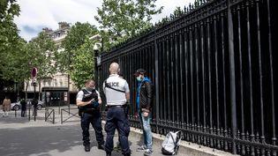 Un contrôle d'identité par des policiers sur la voie publique pendant le déconfinement à Paris, le 12mai 2020. (BRUNO LEVESQUE / MAXPPP)