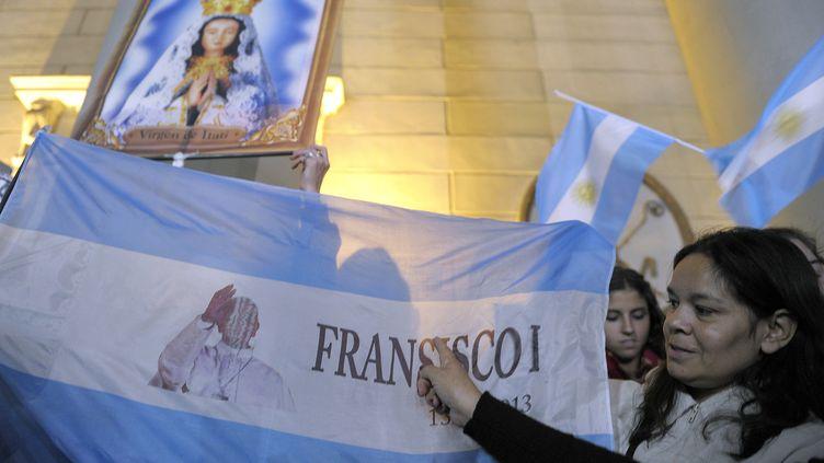 Une Argentine arbore un drapeau aux couleurs de son pays et du pape François, le 13 mars 2013 à Buenos Aires (Argentine). (ALEJANDRO PAGNI / AFP)