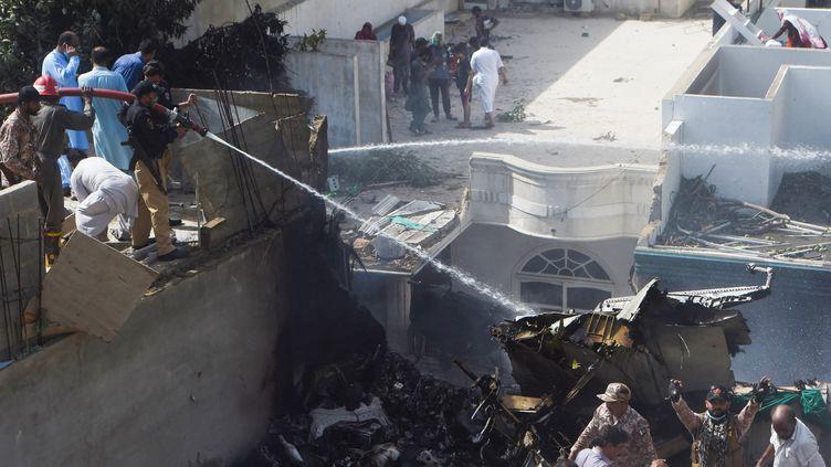 Des policiers utilisent des lances à eau après le crash d'un avion de la Pakistan International Airlines dans un quartier résidentiel de Karachi, vendredi 22 mai 2020. (ASIF HASSAN / AFP)