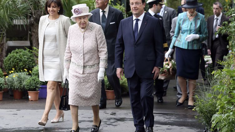 La reine Elizabeth II, le président de la République François Hollande et la maire de Paris Anne Hidalgo visitent le marché aux fleurs, sur l'île de la Cité à Paris, samedi 7 juin 2014. (FRANCOIS LENOIR / POOL)