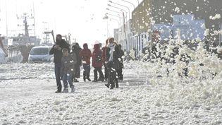 Non, ce n'est pas la neige, mais bien l'écume qui envahit les rues de Saint-Guénolé (Finistère), pour le plus grand plaisir des passants. (MAXPPP)