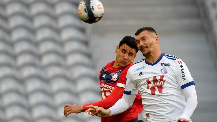 Benjamin André et Ludovic Ajorque se battent pour le ballon. (DENIS CHARLET / AFP)