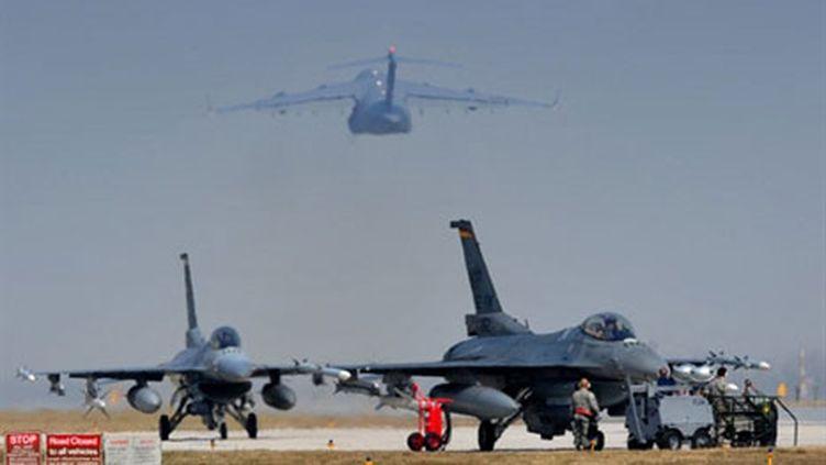 Deux F16 de l'armée américaine sont stationnés alors qu'un C17 décolle du tarmac d'une base italienne, le 25 mars 2011. (AFP - Giuseppe Cacace)