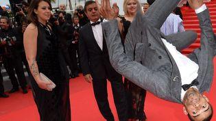 Le tapis rouge la tête en bas, c'est comment ? Le danseur Brahim Zaibat a une façon bien à lui de monter les marches...  (ALBERTO PIZZOLI / AFP)