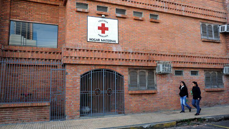 Deux femmes passent devant un hôpital d'Asuncion (Paraguay) où est hospitalisée une fillette de 10 ans, tombée enceinte après un viol, le 8 mai 2015. (NORBERTO DUARTE / AFP)