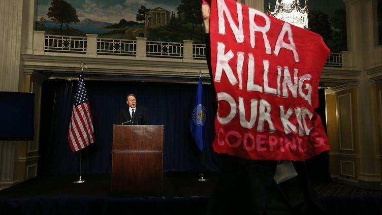 Un manifestant interromptla conférence de presse du vice-président de la NRA, Wayne LaPierre, le 21 décembre 2012 à Washington (Etats-Unis). (ALEX WONG / GETTY IMAGES NORTH AMERICA / AFP)