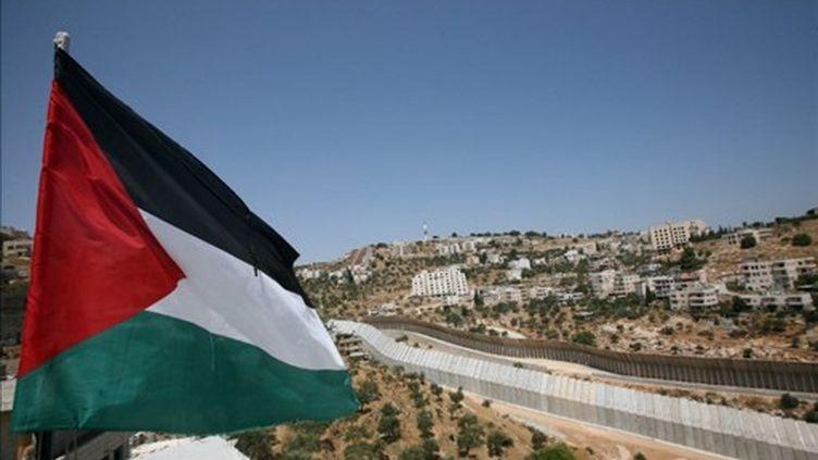 """Le drapeau palestinien en face du """"mur de séparation"""" en Cisjordanie (AFP)"""