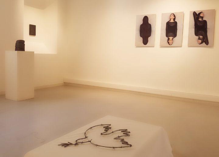 """Au premier plan : """"Guerre et Paix"""" de Faten Gaddes (sculpture métal) - Au second plan : """"Mujeres"""" photos de Mouna Jemal Siala  (Aude Meier)"""