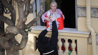 En période de confinement Covid-19, certaines personnes n'ont d'autre choix que de se faire livrer. Un livreur passe le colis par la fenêtre afin d'éviter tout contact, le 29 mars à Nice (Alpes-Maritimes). (ARIE BOTBOL / HANS LUCAS / AFP)