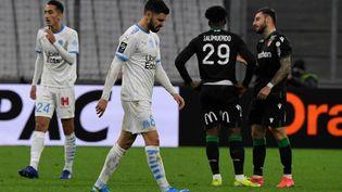 Le bonheur des Lensois au Vélodrome de Marseille et la détresse de Morgan Sanson, le joueur de l'OM, le 20 janvier 2021lors d'un match de Ligue 1. (NICOLAS TUCAT / AFP)