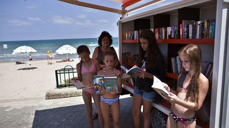 Des jeunes filles consultent des livres dans la bibliothèque mobile installée sur une plage de Tel Aviv (Israël), le 9 juillet 2013. (NIR ELIAS / REUTERS)