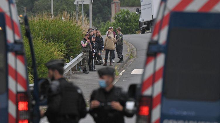 Des gendarmes barrent une route à quelques mètres du lieu où se déroule une fête interdite à Redon (Ille-et-Vilaine), le 19 juin 2021. (LOIC VENANCE / AFP)