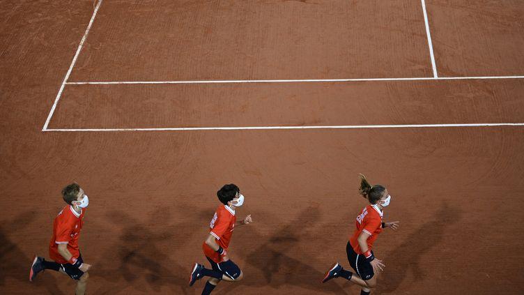 Des ramasseurs de balles courent sur le court de tennis le troisième jour de Roland-Garros à Paris, le 29 septembre 2020. (ANNE-CHRISTINE POUJOULAT / AFP)