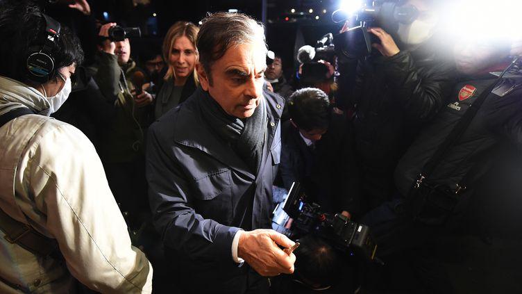 Carlos Ghosn et son épouse Carole entouré de journaliste à leur arrivée à leur résidence à Tokyo, le 3 avril 2019. (CHARLY TRIBALLEAU / AFP)
