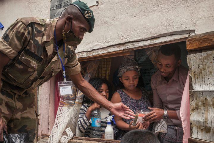 Des soldats de l'armée malgache distribuent des masques et des sachets d'herbes à infuser contre le coronavirus, le 22 avril 2020, dans le centre-ville d'Antananarivo. (RIJASOLO / AFP)