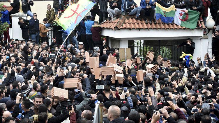 Des manifestants brandissent le drapeau berbère et des briques pour dire non à la présidentielle, à Tizi Ouzou, le 8 décembre 2019. (RYAD KRAMDI / AFP)