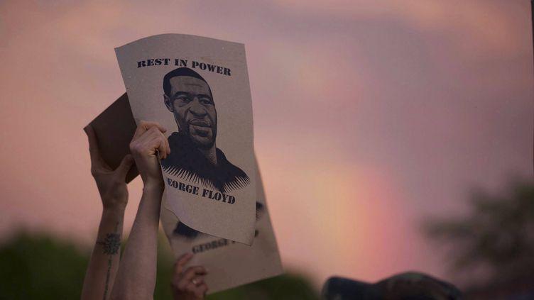 Un manifestant brandit un portrait de George Floyd lors d'une manifestation, à Minneapolis (Minnesota, Etats-Unis), le 27 mai 2020. (CHRISTINE T. NGUYEN / AP / SIPA)