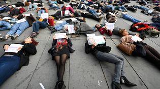 """Des militantes féministes effectuent un """"die-in"""", le 19 octobre 2019, sur la place de la République à Paris, pour sensibiliser le grand public à la question des féminicides. (DOMINIQUE FAGET / AFP)"""